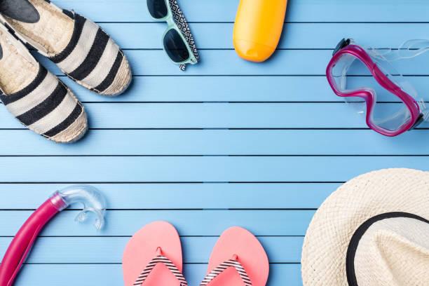 summer holiday background with beach accessories on blue wooden plank - salzwasser sandalen stock-fotos und bilder