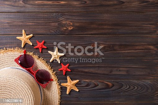699960484istockphoto summer holiday beach background with accessories on wooden table, top view with copy space. vacation concept 1160228516
