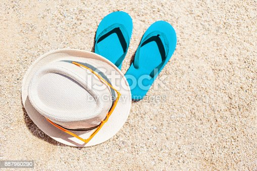 istock Summer holiday beach background with flip flops and hat  on a tropical beach. Slippers on a  sand with copyspace 887960290