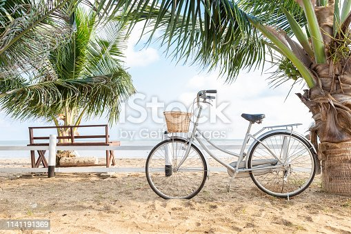 Summer holiday concept background, coconut tree and bicycle on the beach