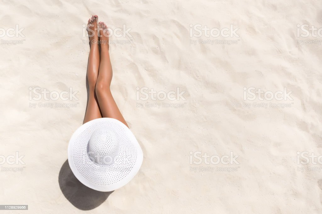 Summer holiday fashion concept - tanning woman wearing sun hat at the beach on a white sand shot from above Summer holiday fashion concept - tanning woman wearing sun hat at the beach on a white sand shot from above Adult Stock Photo