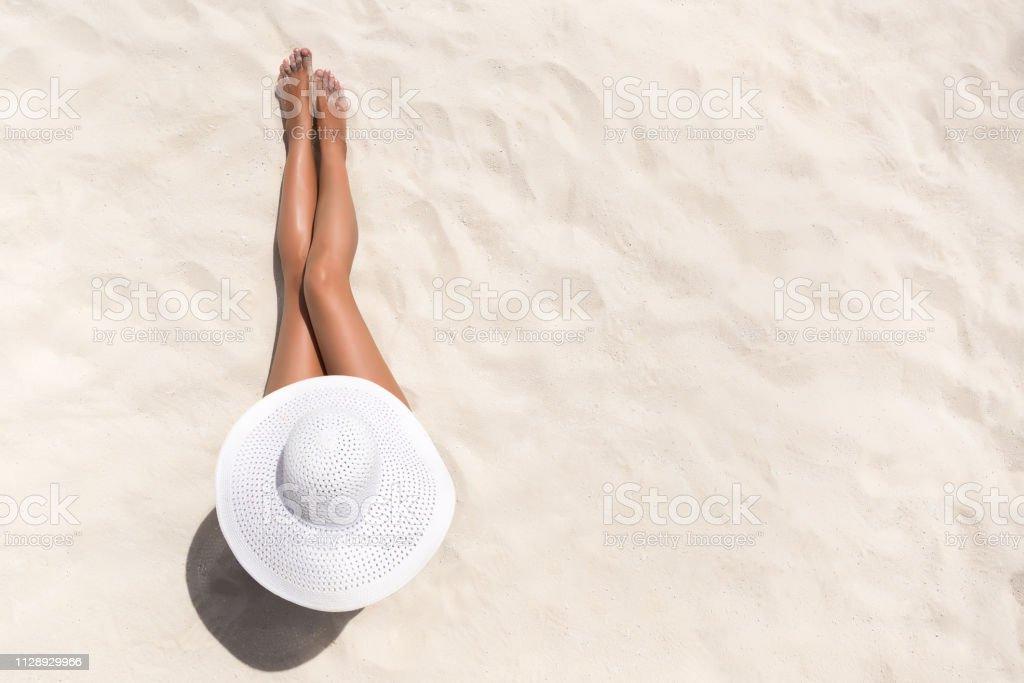 夏季節日時尚概念-曬黑婦女戴太陽帽子在海灘上從上面拍攝的白色沙子 - 免版稅人的腳圖庫照片