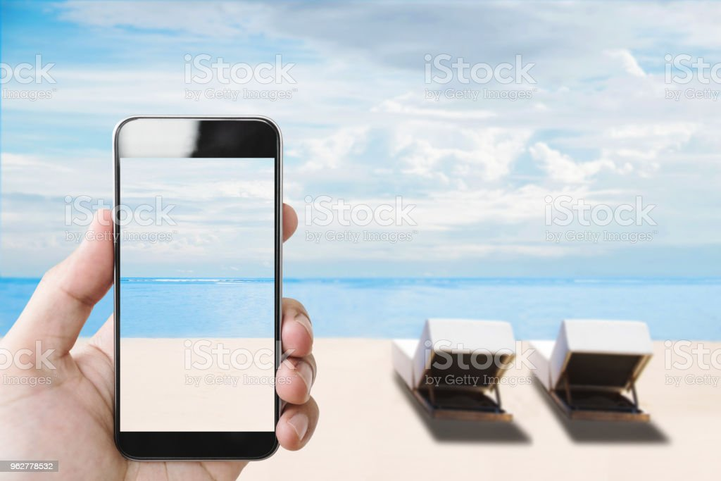 Summer holiday, hand holding mobile smartphone on the beach in summer - Foto stock royalty-free di Ambientazione esterna