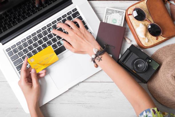 Sommerurlaub, Hand Menschen halten Kreditkarte online buchen Reisen auf Laptop unter weißen hölzernen Hintergrund. – Foto