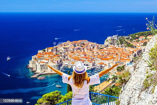 Happy young girl enjoys view of old town (medieval Ragusa) and Dalmatian Coast of Adriatic Sea in Dubrovnik. Blue sea with white yachts, beautiful landscape, aerial view, Dubrovnik, Croatia