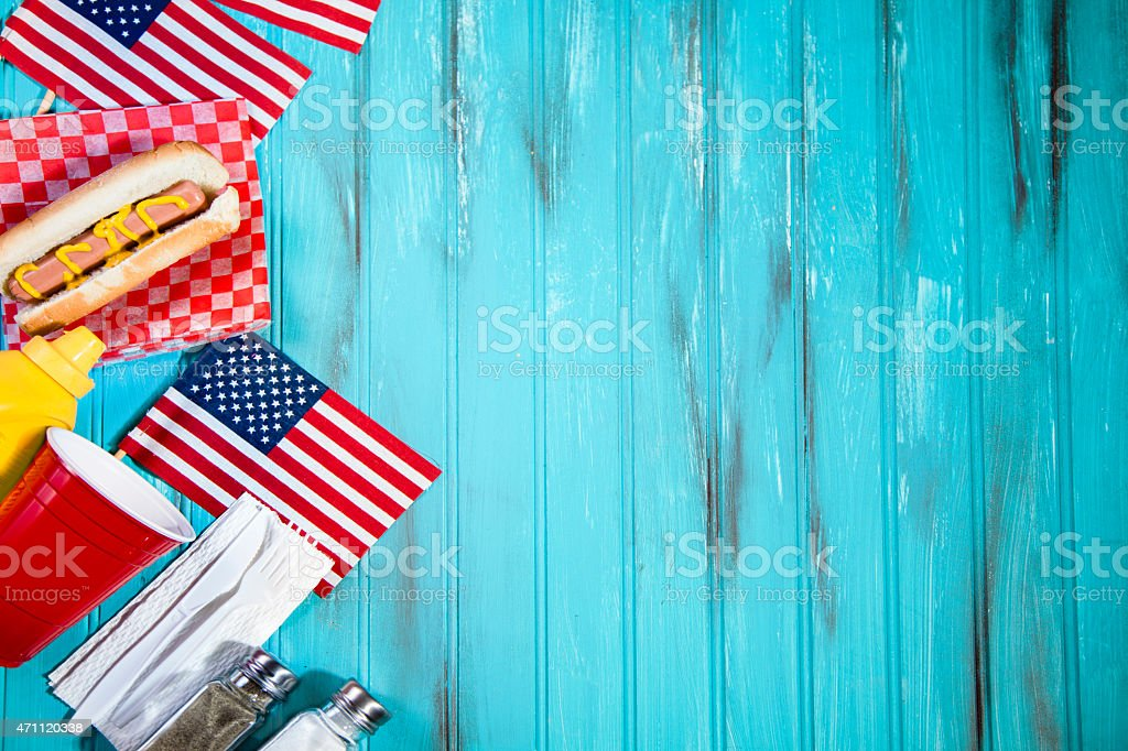 Férias de verão piquenique.   Cachorros-quentes, EUA flags.   Blue Mesa de madeira. - foto de acervo
