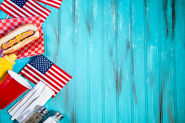 Summer holiday picnic. Hot dogs, USA flags. Blue wooden table. stock photo