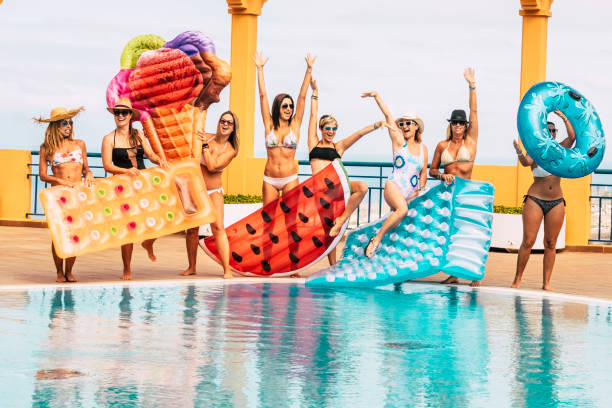 Summer holiday vacation at the pool - travel and enjoy the friendship for young beautiful people - group of women in bikini have fun with coloured trendy lilos inflatables - enjoying outdoor together stock photo