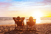 summer holidays, beach travel, vacation for couple, man and woman relax and enjoy life together at sunset