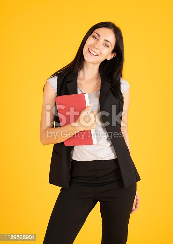 1176252245 istock photo Summer holidays. Campus and teenage concept. Education first. Beautiful female college student holding her books smiling happily standing isolated on yellow background. 1189568904
