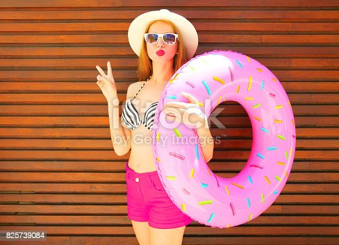 Summer holidays concept - pretty woman holds inflatable ring on wooden background