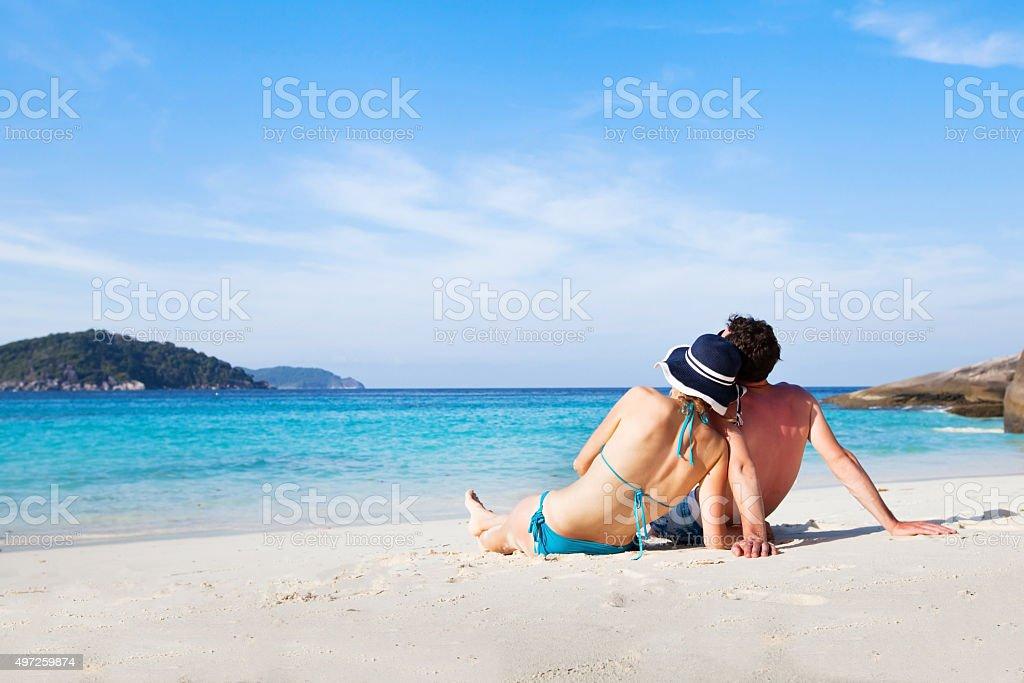 summer holidays, couple sitting on paradise beach stock photo