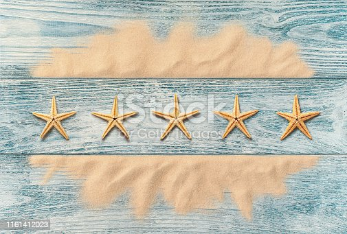 istock Summer holidays, five star service concept, high angle view of starfish on the wooden background 1161412023