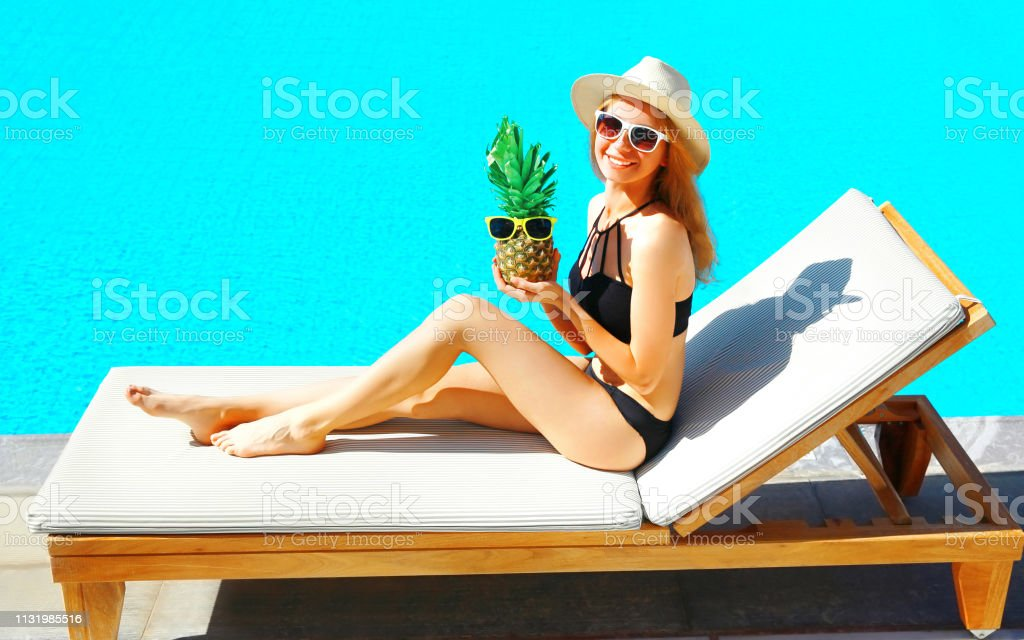summer holidays - happy smiling woman lies on deckchair with pineapple over blue water pool background stock photo