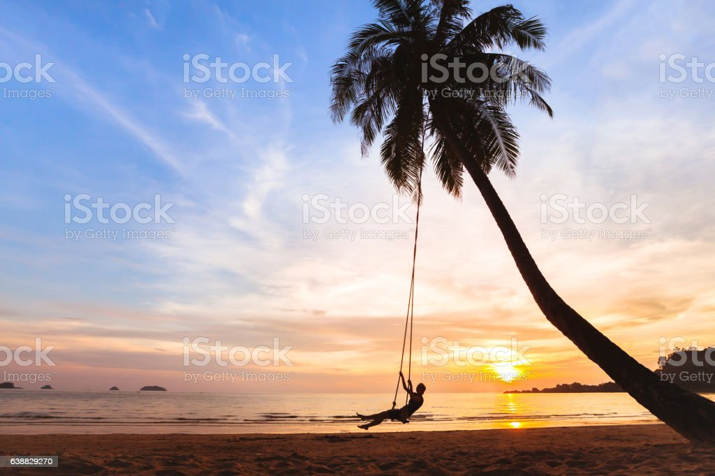 summer holidays, happy woman on beach swing stock photo