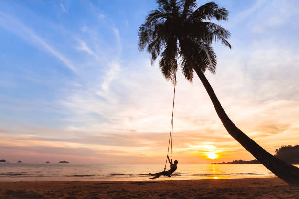 summer holidays, happy woman on beach swing summer holidays, happy woman on the swing on tropical beach at sunset koh chang stock pictures, royalty-free photos & images