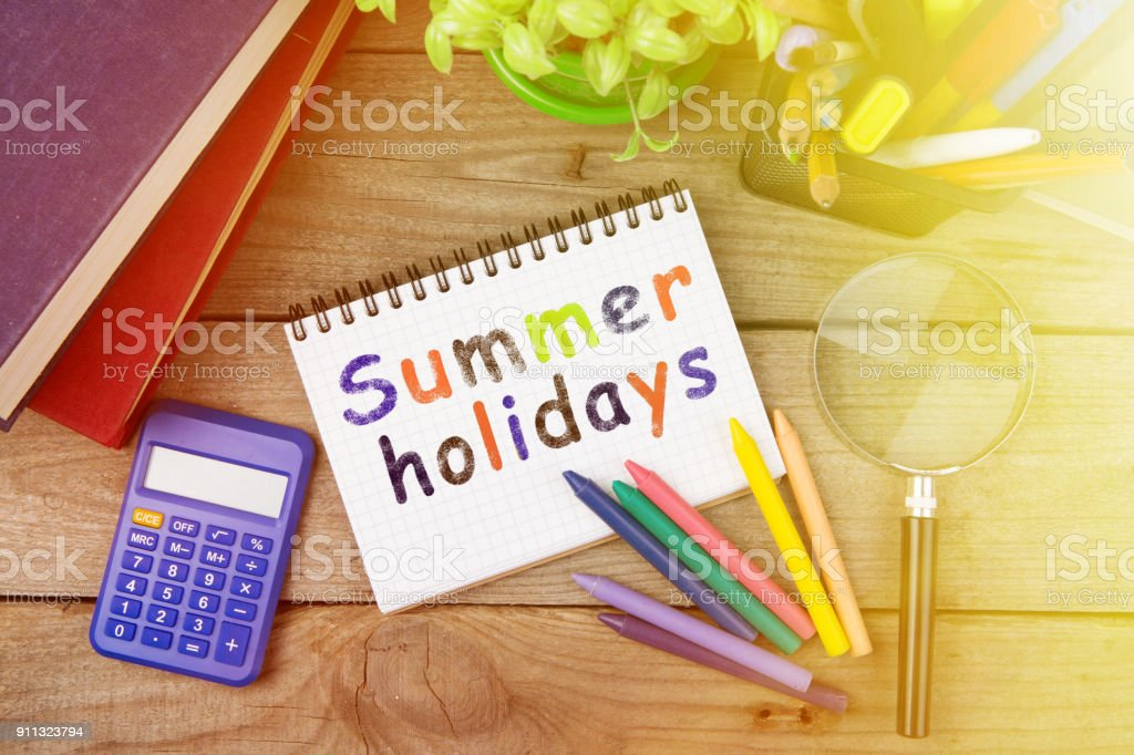 summer holidays inscription with crayons and notepad on the wooden table stock photo