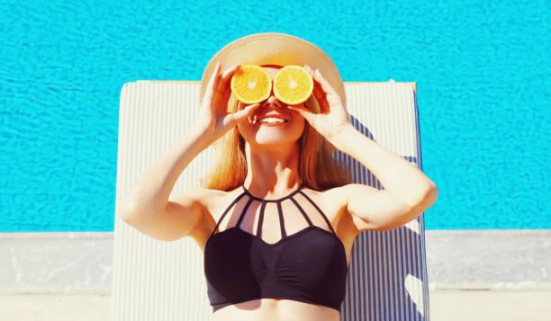 Sommerferien-Porträtfrau, die in ihren Händen Orangenscheiben hält, die ihre Augen auf blauem Wasserbecken verstecken – Foto
