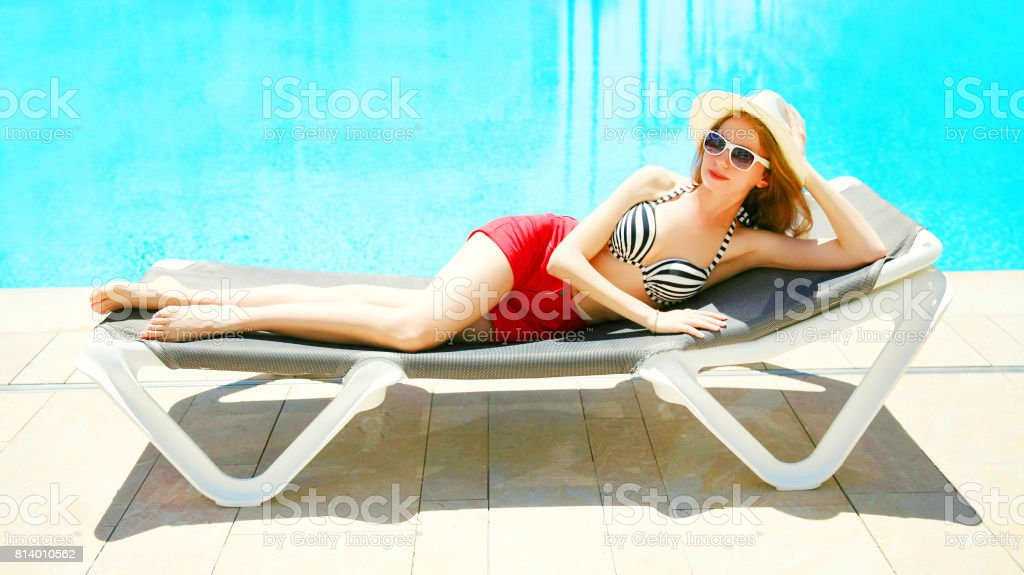 Summer holidays - pretty woman lying on a deckchair over a blue water pool background stock photo