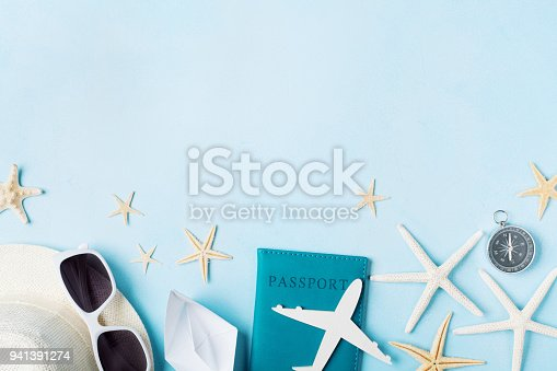 936373320 istock photo Summer holidays, vacation, travel and tourism background from sunglasses, hat, passport, airplane and boat miniatures, starfish. Top view. 941391274