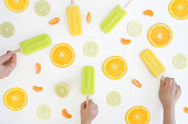 Summer ice blocks in orange, green and yellow colours and flavours on a white background. Food background and texture