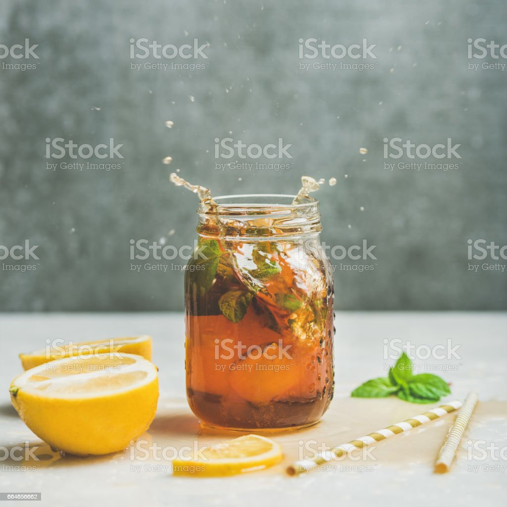 Summer Iced tea with lemon and herbs, square crop stock photo