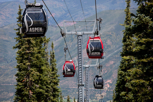 Aspen, Colorado, USA - August 20, 2011: Summer in Aspen, Colorado, remains a popular tourist travel destination despite the lack of snow.  The red gondola lifts have been updated to feature solar panel powered iPod connectivity so passengers can listen to their personal music while using the gondola.