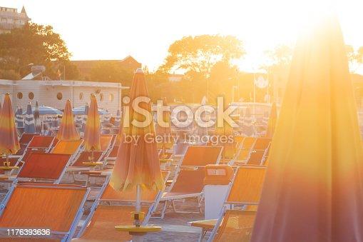 Summer in Rimini, Italy. Sun umbrellas and deck chairs on sandy sea beach in Rimini. Summer resort vacation on seashore