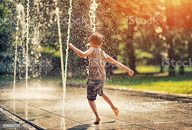 Hot summer day in the city. Little boy is having fun playing in the park fountain. He is running barefeet getting wet and splashing.