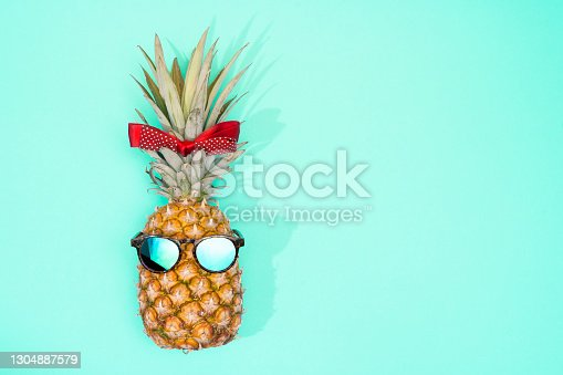 Pineapple with sunglasses and hair bow on blue background