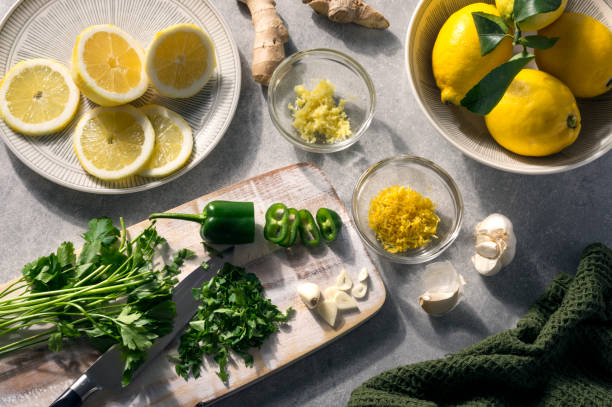 Summer ingredients, fresh green and yellow spices and flavours. Parsley, lemon, garlic, green chilli and ginger. Rustic scene on a sunny table. Alternative medicine concept. stock photo