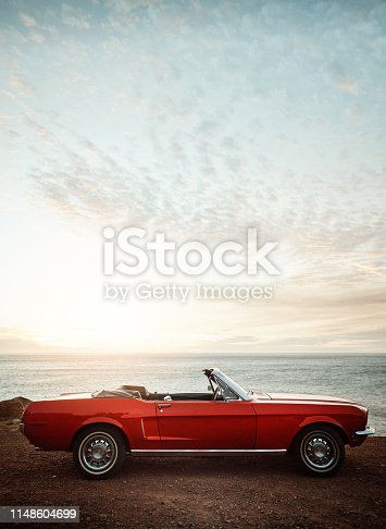 Shot of an empty vintage car parked along the coast at sunset