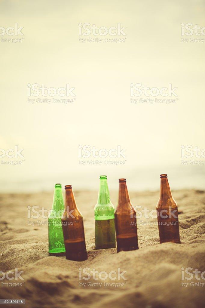 Summer is here: beer bottles left on the beach stock photo