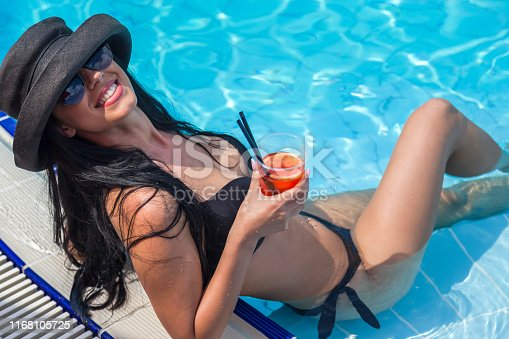Beautiful young woman wearing bikini in swimming pool with sun hat and cocktail