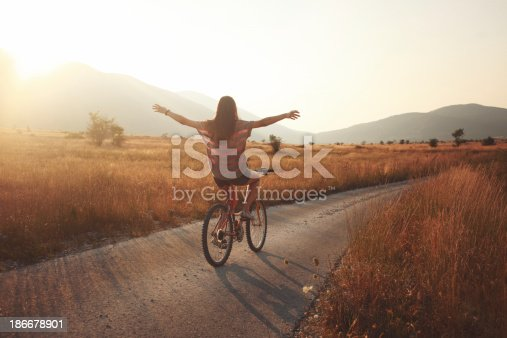 vintage toned young brunette on a bicycle, lit by the Autumn sunset.