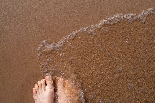Women standing on the clean sandy beach with wave motion coming to their feet. Top view of woman feet on the sand.