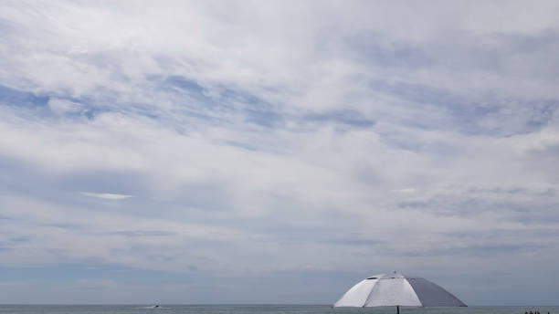 Summer landscape with sea skyline and top of silver color sunshade in corner of frame. Tranquil cloudscape. Cloudy background in shades of light blue and white. High sky scenery. Windy weather day. stock photo