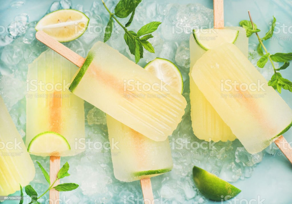 Summer lemonade popsicles with lime and chipped ice, top view stock photo