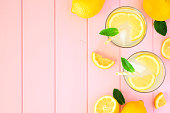 Sweet summer lemonade. Top view side border with copy space on a pastel pink wood background.