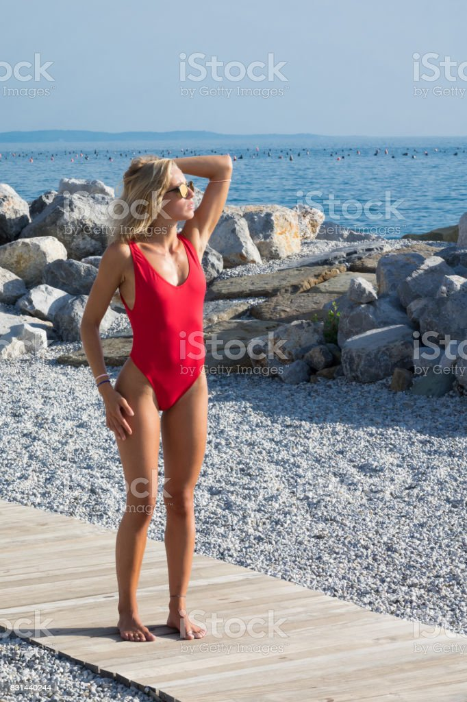 Sexy Tanned Girl In Red One Piece Swimsuit On The Beach Royalty