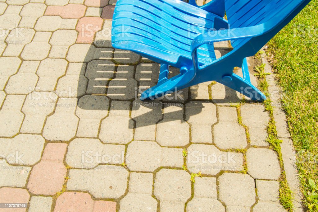Summer Lounge Area By The Outdoor Pool Modern Empty Plastic Blue Chaise Longue Stand In A Row On The Paving Tiles On A Hot Summer Sunny Day Copy Space Stock Photo