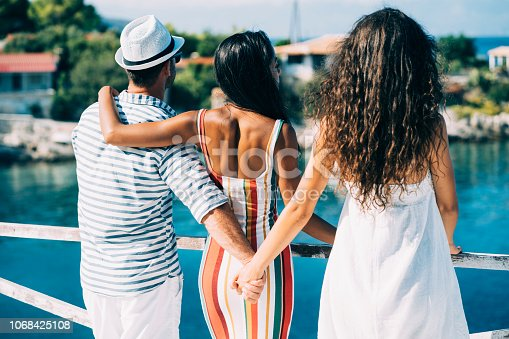 Couple in vacations standing on harbor, man hoding other woman's hand.