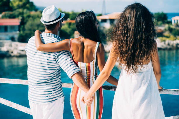 Summer love triangle Couple in vacations standing on harbor, man hoding other woman's hand. dishonesty stock pictures, royalty-free photos & images