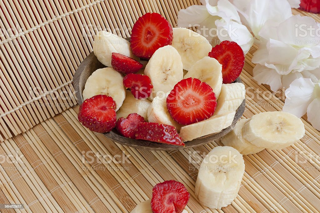 Summer lunch: cut bananas and strawberries royalty-free stock photo