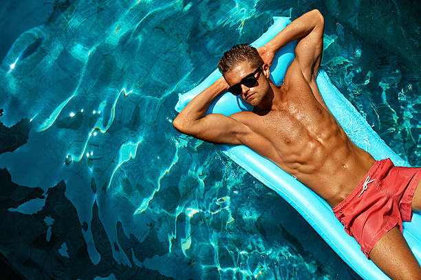 summer man body care. beautiful male relaxing in pool - sexe symbole photos et images de collection