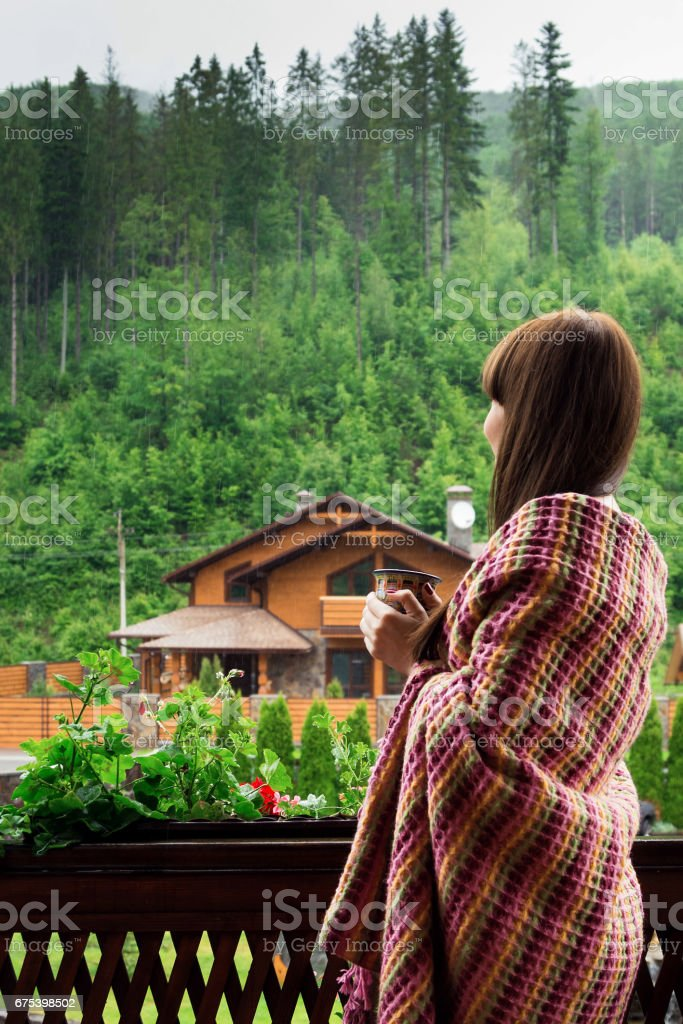 Summer morning in mountains Carpathians. A young woman wrapped in a blanket with a cup in hand. photo libre de droits