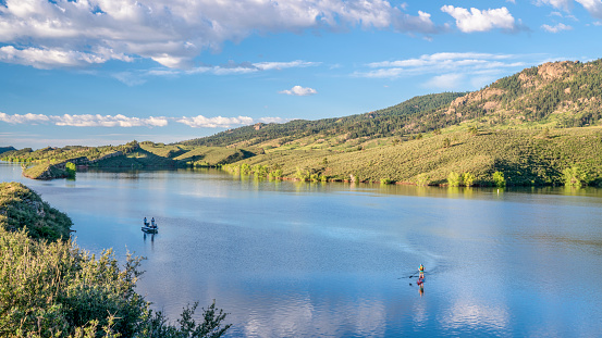 summer morning on Horsetooth Reservoir at foothills of Rocky Mountains in northern Colorado with a fishing boat and a stand up paddler, popular recreation destination in Fort Collins area