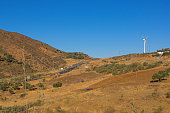 Summer mountain landscape. A highway, the groves of young olive trees, the wind power generator in sunny day. Spain, Andalusia.