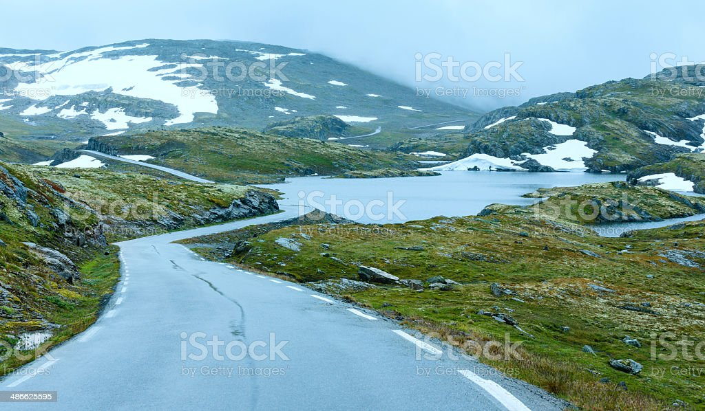 Summer mountain with lake and road (Norway) Summer mountain misty landscape with road, lake and snow (Norway, Aurlandsfjellet). Cloud - Sky Stock Photo