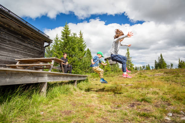 Summer nature side view of children in mid air jumping off a porch landing on grass hill. stock photo